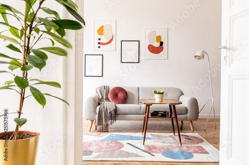 Fotografija  Elegant retro living room with design grey sofa, coffee table, lamp, plants and furniture