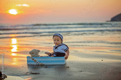 Fotografiet  Sailor baby boy, cute child, playing on the beach with wooden boat, fishes and f