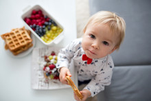 Sweet Toddler Birthday Boy, Eating Belgian Waffle With Raspberries, Blueberries, Cocnut And Chocolate