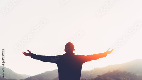 Carta da parati Copy space of man rise hand up on top of mountain and sunset sky abstract background