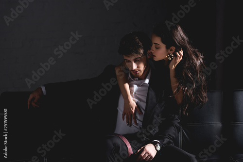 brunette woman in black dress standing behind couch, hugging and kissing handsome man in suit sitting on black background