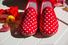 Beautiful Red Colorful Children's Shoes In The Peas. Lie On A White Wooden Floor.red Colorful Child Boots In Peas. Modern Stylish Fashionable Trendy Multicolored.Shoes For Children. Baby Sneakers