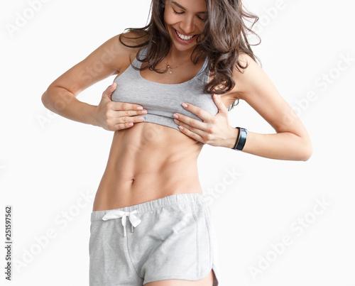 Photo Slim happy sportswoman showing abs