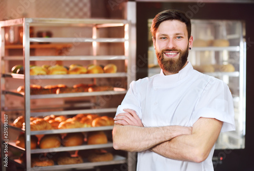 Fototapeta  Young handsome male baker in white uniform against a background of baking and bread