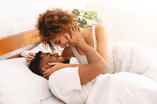 Happy Black Young Couple Kissing In Bed