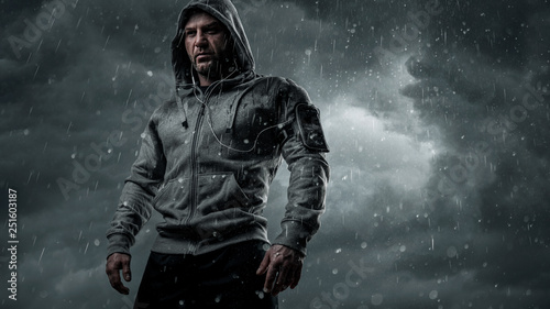 Obraz na płótnie Dark, dramatic portrait of a runner standing in the rain with copy space