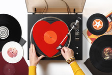 A Red Heart Vinyl Record Turntable On A White Table With Plates. Included Gramophone, Torque. The Hand Of A Girl DJ With Bright Accessory Puts A Stylus With A Needle On A Vinyl Record. Valentine's Day