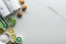 Top View Of Natural Ingredients For Handmade Cosmetics, Towels And Bottles On White Surface