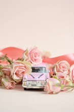 Pink Toy Car Surrounded By A Bouquet Of Spray Roses. Free Space To Place Text. The Concept Of Holiday Greetings. Light Background. Vertical Frame Orientation.