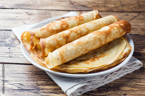 Thin pancakes on a plate. Wooden background. Close up. Wallpaper Mural