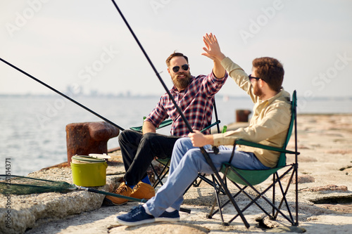 Poster Peche leisure and people concept - happy friends with fishing rods on pier at sea