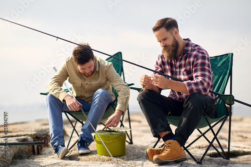 Fotografie, Obraz  leisure and people concept - friends or fishermen adjusting fishing rods with ba