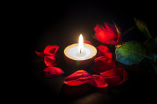 Tea Candle, Red Rose And Rose Petals On Black