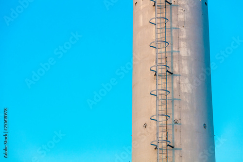 Canvas Prints Birds in the forest Close-up industrial chimney with ladders in pastel blue sky background