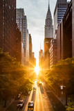 Fototapeta Nowy York - Sunset light shining on the buildings and cars on 42nd Street in Midtown New York City around the time of the Manhattanhenge summer solstice