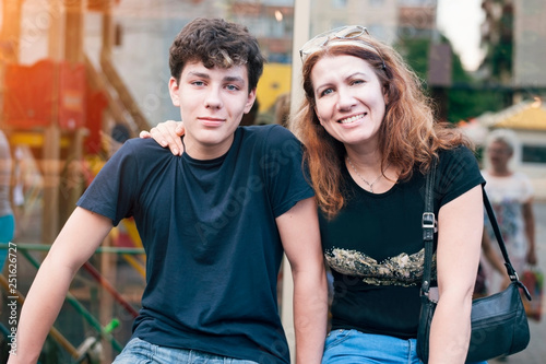 Fotografiet  Happy mother hug her teenage son and rejoices because she is reconciled with her