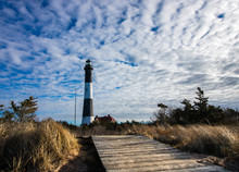Boardwalk Leading To A Lighthouse On A Clear Blue Day With Movement In The Clouds Behind It.