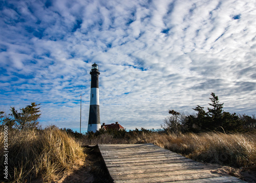 Foto  Boardwalk leading to a Lighthouse on a clear blue day with movement in the clouds behind it