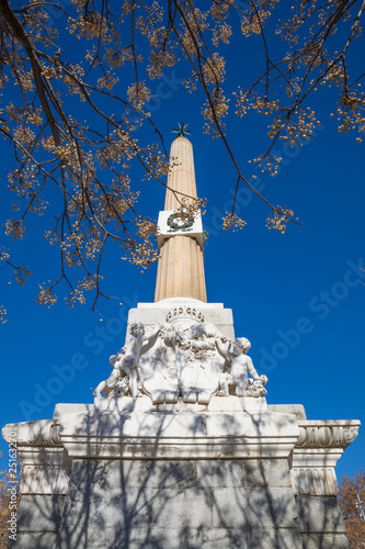 Photo tree branch, blue sky and obelisk of Arganzuela, landmark and monument from year