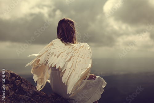 woman with wings sitting on a rock and looking on horizon of mountains. angel - 251639133