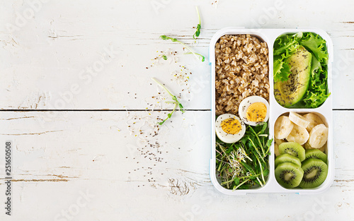 Foto op Aluminium Kruidenierswinkel Lunch box with boiled eggs, oatmeal, avocado, micro greens and fruits. Healthy fitness food. Take away. Lunchbox. Top view