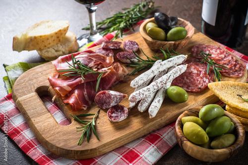 Fényképezés  Antipasto delicatessen - sliced meat, ham, salami, olives on wooden board