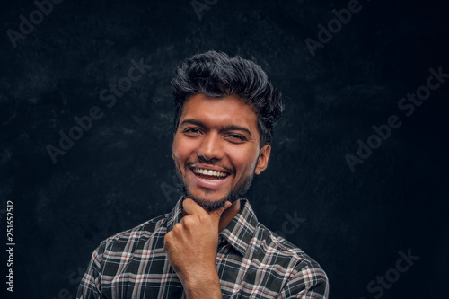 Close-up portrait of a handsome Indian man wearing a plaid shirt posing with hand on chin, smiling and looking at a camera Canvas Print