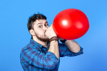 Man Inflating A Red Balloon By Mouth, Image On A Blue Background
