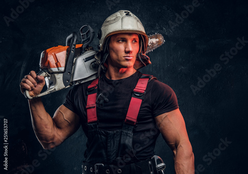 Fotografía  Young lumberjack wearing protective clothes posing with a chainsaw and looks sid
