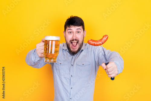 Fényképezés man with a glass of beer and grilled sausage on a fork in his hand, standing on