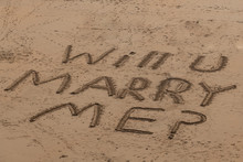 "Aerial View Of The Words ""Will U Marry Me"" Written In Sand, On A Beach In Wales"
