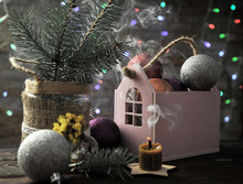 Christmas Composition With A Candle, A House And Christmas Decorations On A Table Against The Background Of Colored Garlands.