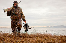 Satisfied Duck Hunter Wearing Camouflage Clothing Carrying Two Dead Ducks And Shotgun As He Walks Along Edge Of A Lake.
