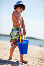 Young Boy With Bucket Of Sand.