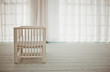 Empty white crib in a white room waiting for a baby.