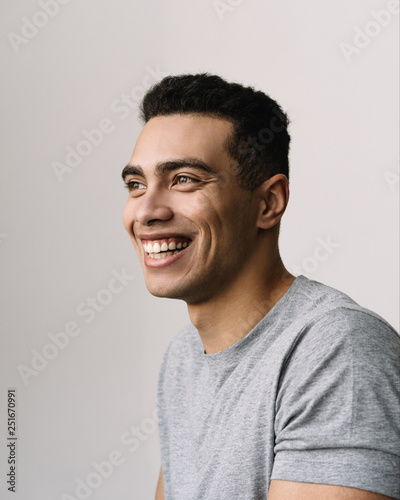Fototapety, obrazy: Authentic portrait of handsome smiling African American man with happy emotional face, wearing grey casual t shirt. Positive fashion model posing for pictures in studio, isolated on white background
