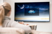 Woman Watches Tv With 8k Ultra Hd Resolution. Picture On The Screen Created In Graphic Software.
