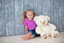 Adorable Smiling Little Girl Sitting Near A Gray Wooden Wall Background And Hugging A White Teddy Bear