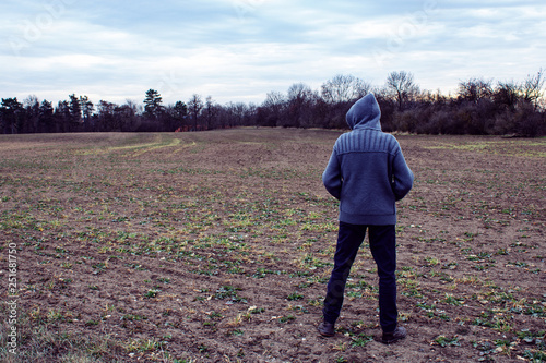Fotografía  Conceptual anonymous unidentified person in hood is standing on field and lookin