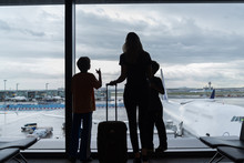 Silhouettes Of Mom With Kids In Terminal Waiting For Flight Travel Concept