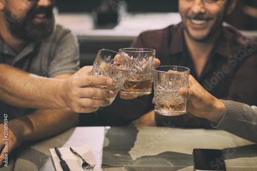 Pinturas sobre lienzo  Close up of unrecognizable men clinking crystal glasses with alcoholic beverage
