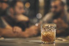 Close Up Of Crystal Glass Of Whiskey, Brandy Or Scotch Placed On Table. Behind People Sitting In Bar, Communicating And Drinking Alcohol. Concept Of Delicious Elite Alcohol.