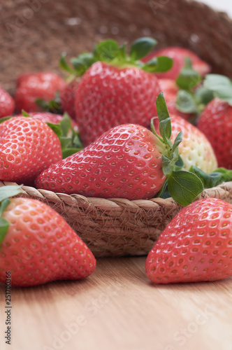 Fotografía  close up fresh strawberries with natural wood background in a basket