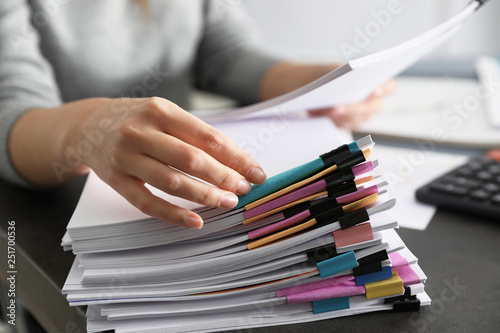 Slika na platnu Office employee working with documents at table, closeup