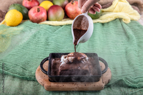 Photo sizzling chocolate brownie is a sweet dish made using scoop of ice-cream on top served with a generous pouring of melted chocolate