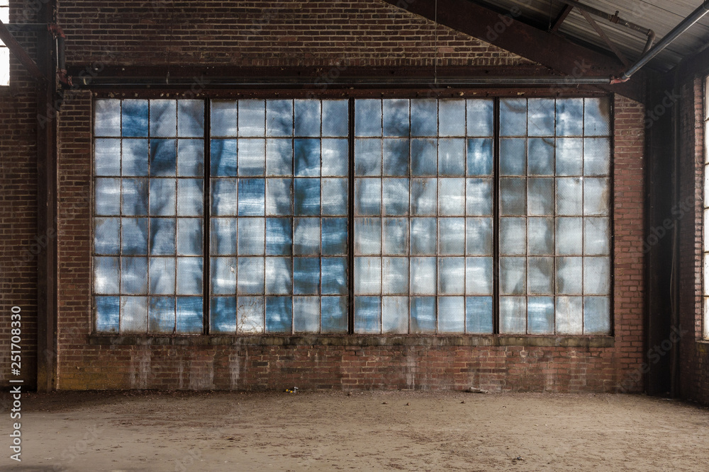 Fototapety, obrazy: Large blue frosted windows in a loft like space of an abandoned factory with brick walls