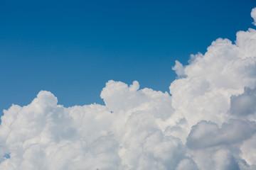 puszyste białe chmury nad jasnym tle niebieskiego nieba