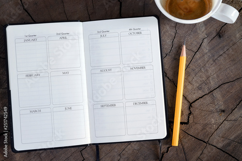 Photo Top view of open page diary with yellow pencil and cup of coffee on wooden background