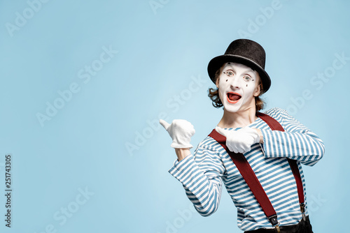 Photo Emotional pantomime with white facial makeup showing empty space on the blue bac