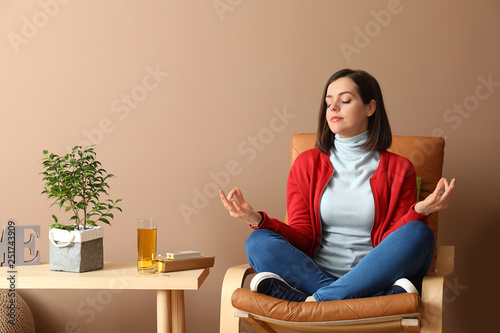 Young woman meditating in armchair at home